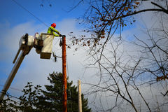 Electrical Worker fixing Electrical Pole Wires. An electrical worker installing new electrical lines on an electric pole in a cherry picker basket Stock Images