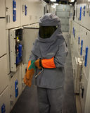 Electrical worker in protective gear. An Electrical worker wearing arc-flash protection. The tool in his hand is used to draw out a large circuit breaker royalty free stock image