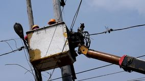Electrical Workers On Telehandler With Bucket installing High tension wires. San Pablo City, Laguna, Philippines - February 26, 2018: Electrical Workers On stock video footage