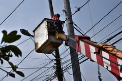 Electrical Workers On Telehandler With Bucket installing High tension wires on tall concrete post. Underside view low angle Royalty Free Stock Photos