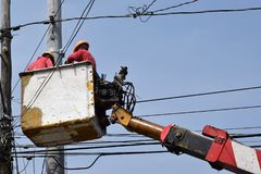 Electrical Workers On Telehandler With Bucket installing High tension wires on tall concrete post. Underside view low angle Stock Photography
