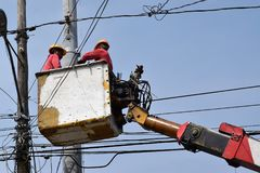 Electrical Workers On Telehandler With Bucket installing High tension wires on tall concrete post. Underside view low angle Stock Photo