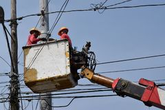 Electrical Workers On Telehandler With Bucket installing High tension wires on tall concrete post. Underside view low angle Royalty Free Stock Image