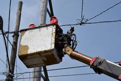 Electrical Workers On Telehandler With Bucket installing High tension wires on tall concrete post. Underside view low angle Royalty Free Stock Images