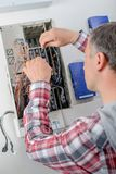 Electrican at fuse box. Adult royalty free stock photos