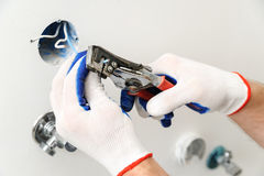 Electrican stripping insulation from wire. Royalty Free Stock Image