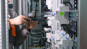 Electricequipment de instalación electircian irreconocible, trituradores en la caja del fusible eléctrico en la fábrica industria almacen de metraje de vídeo
