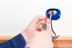 Electrician. Electrisian mounting a power outlet in wall Stock Photo