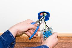 Electrician. Electrisian cutting wire and demounting power outlet Royalty Free Stock Image