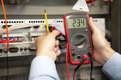 Electrician adjusts electrical control panel royalty free stock photos