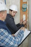 Electrician apprentice worker with switching on electric fuse board Stock Images