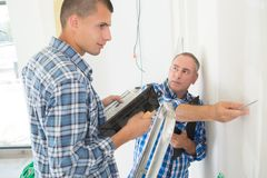 Electrician with apprentice working in new home stock photography