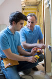 Electrician With Apprentice Working In New Home Stock Photos