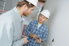 Electrician with apprentice working in new home royalty free stock images