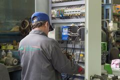 The electrician assembles and adjusts the electrical control cabinet. Works on assembling the electrical circuit of a Stock Photo