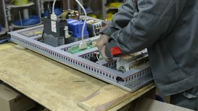 The electrician assembles and adjusts the electrical control panel. Works on assembling the electrical circuit of a metal-cutting machine stock video footage
