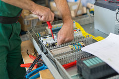 Electrician assembling industrial electric cabinet. Stock Images