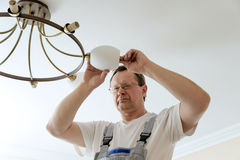 Electrician is attaching a plafond. Stock Photography