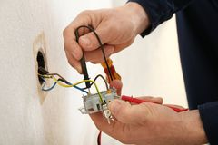 Electrician attaching wires to socket in new building,. Closeup Stock Photo