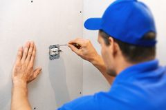 Electrician installing electrical outlet on the wall royalty free stock photo