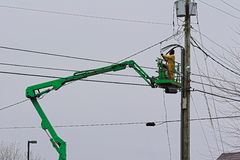 Electrician On Boom. Electrician contractor bringing high voltage lines from new restaurant to be connected to power lines Royalty Free Stock Photo