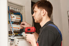 Electrician builder engineer screwing equipment in fuse box. Manually checking qulity Stock Image