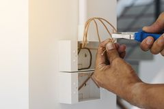 Electrician in the building. Electricians are using a pliers wrench to install the power plug on the wall stock photo