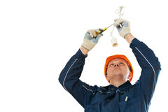Electrician at cable wiring work. One electrician at work laying wiring cable and assembling lamp holder Royalty Free Stock Photo