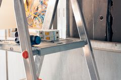 An electrician came to an office space to repair electricity in a room. Used stepladder for repair. On the stepladder are tools and electrical equipment stock photo