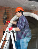 Electrician changing bulb in outdoor lamp on house wall Stock Photo
