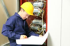 Electrician checking connections in distribution board according to wiring diagram royalty free stock photo