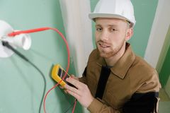 Electrician checking the current. Electrician Royalty Free Stock Photos