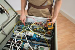 Electrician checking a fuse box Stock Photography