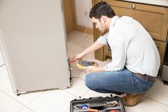Electrician checking voltage on fridge. Attractive young electrician using a multimeter to check the voltage on a broken fridge in a kitchen Royalty Free Stock Image