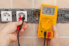 Electrician checking voltage in a partially installed electrical. Wall socket with electronic multimeter Royalty Free Stock Photos