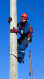 Electrician climbs the pole transmission line Stock Photo