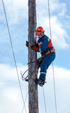 Electrician climbs a power pole Royalty Free Stock Images