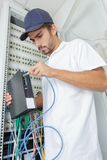 Electrician connect internet server to power board Stock Photos
