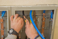 Electrician connecting wires in the electrical cabinet 2 stock photo