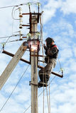 Electrician connects metal parts ground loop on a pole transmiss Royalty Free Stock Photo