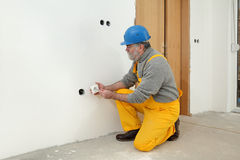 Electrician at construction site install electrical plug Stock Photo