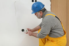 Electrician at construction site install electrical plug Stock Images