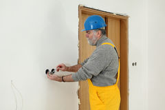Electrician at construction site install electrical plug Royalty Free Stock Photography