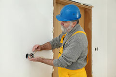 Electrician at construction site install electrical plug Royalty Free Stock Image