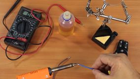 Electrician covers the tinned copper wire with a soldering iron. View from above stock footage