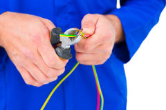 Electrician cutting wire with pliers Stock Photos