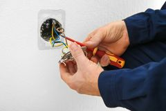 Electrician disassembling wall socket. In new building, closeup royalty free stock photography
