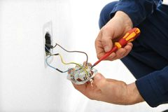 Electrician disassembling wall socket. In new building, closeup stock image