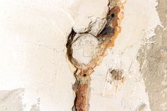 Electrician dismantling broken electric wall socket. On grey bri Stock Image