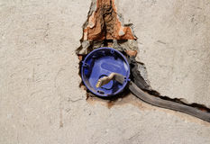 Electrician dismantling broken wall electric socket. On grey con Stock Images